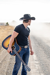 cowboy with a guitar looking down a dirt road