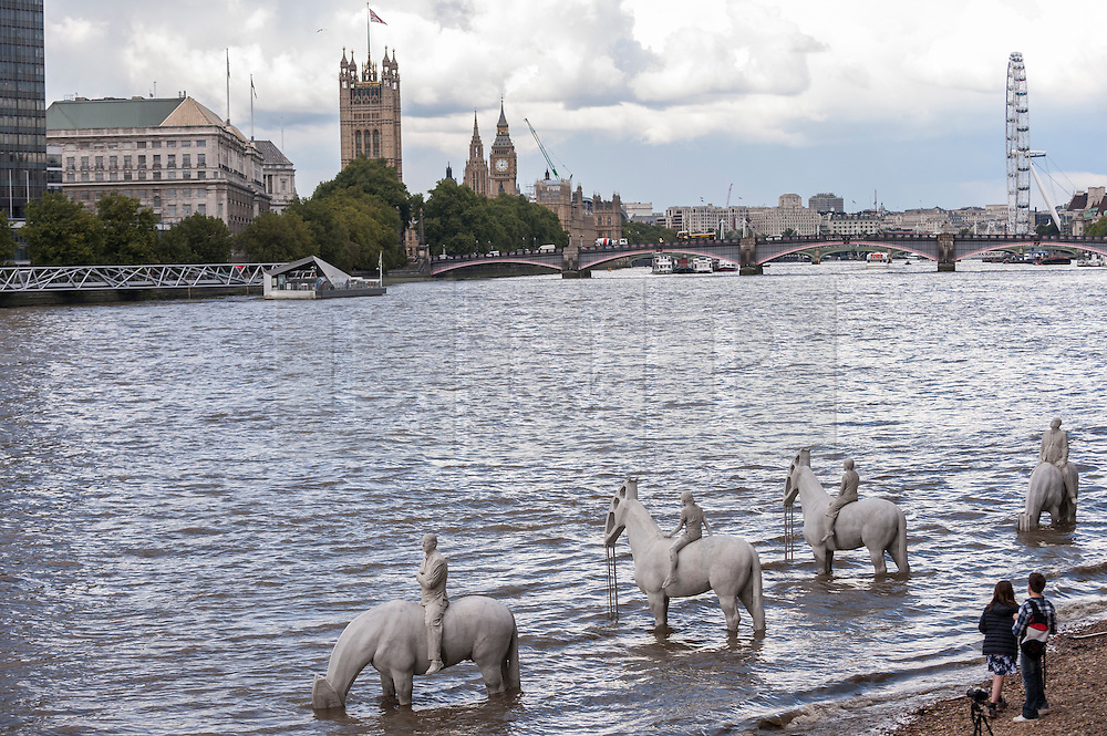 """© Licensed to London News Pictures. 02/09/2015 London, UK. A couple admire the art installation entitled """"The Rising Tide"""" (comprising four horse-riders on horses with petroleum pumps for heads) by the underwater eco-sculptor Jason deCaires Taylor, which stands on the foreshore of the River Thames in Vauxhall and is revealed with each low tide.  The installation aims to question man's reliance on fossil fuels and is part of this year's Totally Thames festival. Photo credit : Stephen Chung/LNP"""
