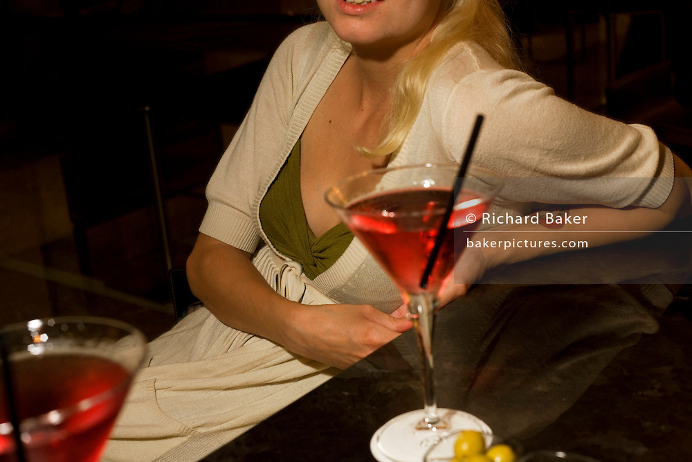 A young lady from sits at a hotel bar with a vodka and cranberry juice cocktail at the Sphere Bar at Heathow Airport