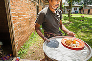 29 OCTOBER 2012 - MAYO, PATTANI, THAILAND: A trustee carries a tray of food to a patient room at the Bukit Kong home in Mayo, Pattani. The home opened 27 years ago as a ponoh school, or traditional Islamic school, in the Mayo district of Pattani. Shortly after it opened, people asked the headmaster to look after individuals with mental illness. The headmaster took them in and soon the school was a home for the mentally ill. Thailand has limited mental health facilities and most are in Bangkok, more than 1,100 kilometers (650 miles) away. The founder died suddenly in 2006 and now his widow, Nuriah Jeteh, struggles to keep the home open. Facilities are crude by western standards but the people who live here have nowhere else to go. Some were brought here by family, others dropped off by the military or police. The home relies on donations and gets no official government support, although soldiers occasionally drop off food. Now there are only six patients, three of whom are kept chained in their rooms.  Jeteh says she relies on traditional Muslim prayers, holy water and herbal medicines to treat the residents. Western style drugs are not available and they don't have a medic on staff.     PHOTO BY JACK KURTZ