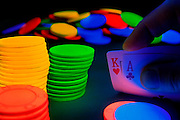 Glowing poker chips illuminate two cards in a high stakes blackjack game.Black light