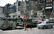 Woman sitting by fishing boats in the harbour at Honfleur,  Calvados, Normandy, France in 1970