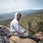 A young African woman hiker takes a break on a rock in the heath zone on Mt Kilimanjaro's Lemosho Trail at about 10,000 feet.