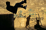 A boy playing on a swing and the shadows of other children on climbing frame in a school yard. in Mazar-I-Shariff, Afghanistan