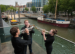 "© Licensed to London News Pictures. 27/07/2015. Bristol, UK.  ""Fanfare for Bristol"", titled ""At the Top of the Tide"", composed by David Mitcham, commissioned by Bristol Proms 2015, performed live for the Mayor of Bristol, George Ferguson and Artistic Director of the Bristol Old Vic, Tom Morris for the first time at Bristol's famous Temple Mead train station, heralding the opening of the Bristol Proms 2015.  David Mitcham's  ""At the Top of the Tide"" was inspired by 'Bristol's inextricable links to the sea'.  The first performance by Arc Brass took place outside the Engine Shed, and throughout the day, performances took place at the Watershed, Pero's Bridge, the Wills Memorial Bell Tower and finally at Bristol Old Vic itself. David Mitcham, who has worked extensively for the BBC Natural History Unit based in Bristol said: ""I am thrilled that my Fanfare ""At the Top of the Tide"" has been chosen for the city of Bristol and to open Bristol Proms 2015. I hope the Fanfare represents the rich diversity of Bristol, its maritime and industrial heritage as well as being a celebration of the spirit of the city and the energy it will carry into the future.""  Bristol Proms 2015 runs from today, 27th July to 1st August and features some of the world's finest musicians including Alison Balsom, Miloš Karadaglić, Pumeza Matshikiza and Daniel Hope.  Photo credit : Simon Chapman/LNP"