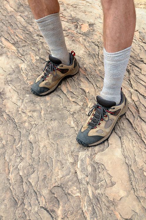 Hiker's legs and feet on sandstone rock in the desert of Southern Utah.