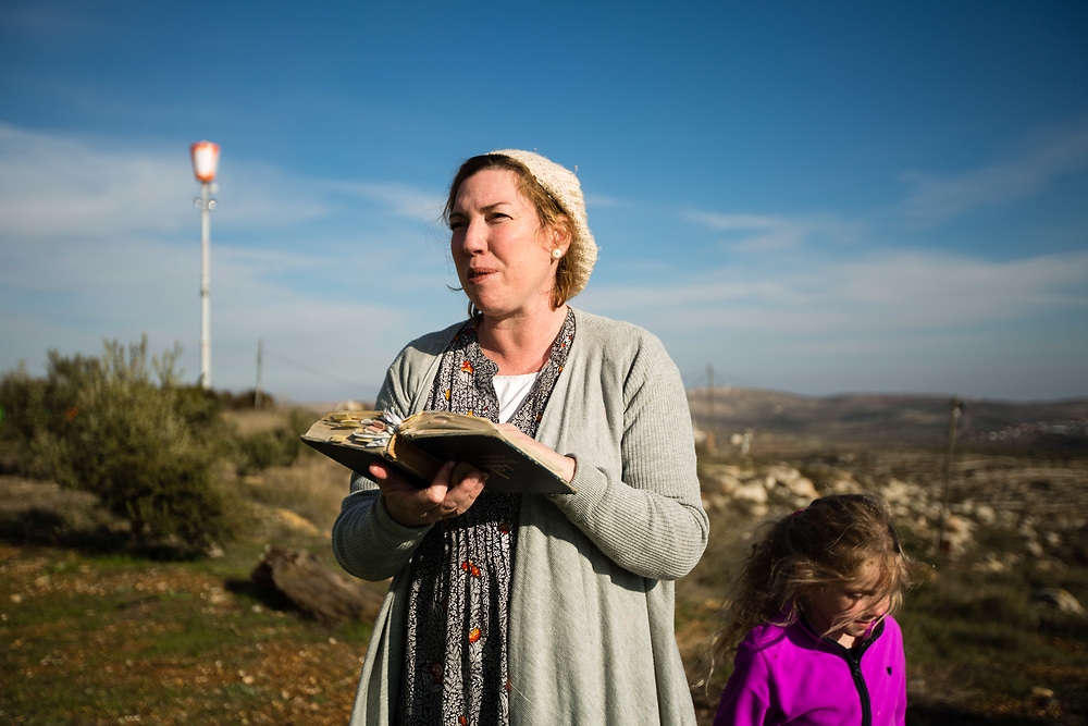 Eliana Passentin reads in the Bible outside her bed and breakfast 'Warm Home with a Breathtaking View' which is advertised on Airbnb international home-sharing site and rental listings service, in the West Bank Jewish settlement of Eli, on January 28, 2016.