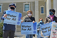 Mineola, New York, USA. April 26, 2021. Activists hold Food and Water Watch group signs saying: Water for All! Faced with a 26% rate increase from New York American Water going into effect May 1, 2021, activists and residents who are NYAW customers rally to urge NYS Assemby to push through legislation, before that date, corresponding with NYS Senate Bill S989A to establish a Nassau County Water Authority and except water works corporations in counties of populations over one million from a special franchise tax.