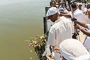 Public radio host of the Roots Musik Karamu show, Osei Chandler drops flower offerings in the water during a remembrance ceremony for enslaved Africans that died in the Middle Passage June 10, 2017 in Sullivan's Island, South Carolina. The Middle Passage refers to the triangular trade in which millions of Africans were shipped to the New World as part of the Atlantic slave trade. An estimated 15% of the Africans died at sea and considerably more in the process of capturing and transporting. The total number of African deaths directly attributable to the Middle Passage voyage is estimated at up to two million African deaths.