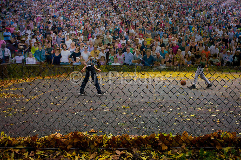 The lower legs of two boys playing basketball, partially intersected by a poster of a crowd - in a south London park. We look through the wire fence of this public space in southeast London in the borough of Lewisham. The faces and bodies of the audience look towards the viewer, a crowd of spectators perhaps created by CGI at some sort of event. And the juxtaposed lower limbs of the boys on the court are in reality playing their own game but still merge with the image, a trick of the eye especially as the legs seem to be matched to individuals.