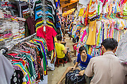 "12 APRIL 2012 - HO CHI MINH CITY, VIETNAM:  Vendors unpack a delivery at a clothing shop in Binh Tay Market. The market is warren of narrow halls and alleys and steep staircases and still relies on manual labor to move goods. Binh Tay market is the largest market in Ho Chi Minh City and is the central market of Cholon. Cholon is the Chinese-influenced section of Ho Chi Minh City (former Saigon). It is the largest ""Chinatown"" in Vietnam. Cholon consists of the western half of District 5 as well as several adjoining neighborhoods in District 6. The Vietnamese name Cholon literally means ""big"" (lon) ""market"" (cho). Incorporated in 1879 as a city 11 km from central Saigon. By the 1930s, it had expanded to the city limit of Saigon. On April 27, 1931, French colonial authorities merged the two cities to form Saigon-Cholon. In 1956, ""Cholon"" was dropped from the name and the city became known as Saigon. During the Vietnam War (called the American War by the Vietnamese), soldiers and deserters from the United States Army maintained a thriving black market in Cholon, trading in various American and especially U.S Army-issue items.            PHOTO BY JACK KURTZ"