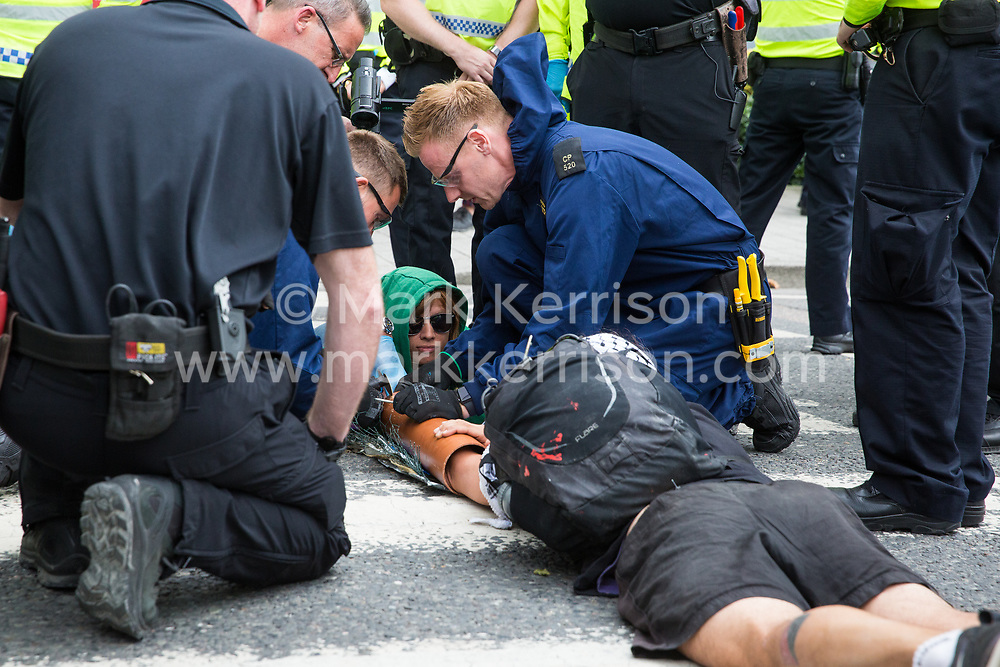 London, UK. 2 September, 2019. Police officers try to remove activists who had locked on using an arm tube to block a road outside ExCel London on the first day of week-long protests against DSEI 2019, the world's largest arms fair. The first day of creative action was hosted by activists calling for a ban on arms exports to Israel and featured workshops, speakers, street theatre and dance. Israeli arms companies display weapons at DSEI marketed as 'combat-proven' following deployment against Palestinian communities.