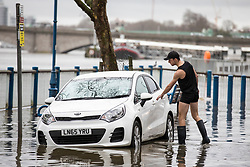 © Licensed to London News Pictures. 02/01/2018. London, UK. A man wades through flood water to rescue his car on the embankment at Putney in West London where the River Thames has broken its banks. Photo credit: Rob Pinney/LNP