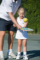 small girl learning to hit a tennis ball on a racquet with help from a tennis instructor