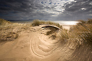 """Nominated in 10th (2017) International Colour Awards (Nature category) <br /> <br /> """"This is from a series I was working on, looking at the amazing shapes created by the force of the wind. Here at Llanddwyn where the dunes face the endless breeze from the Irish Sea, spectacular circular shapes can be found carved into the sandy hills. The light is characteristic of this area, with dark clouds over the mountains and occasional brilliant sunshine bouncing off the surface of the sea. It's wild and elemental but always captivating"""""""