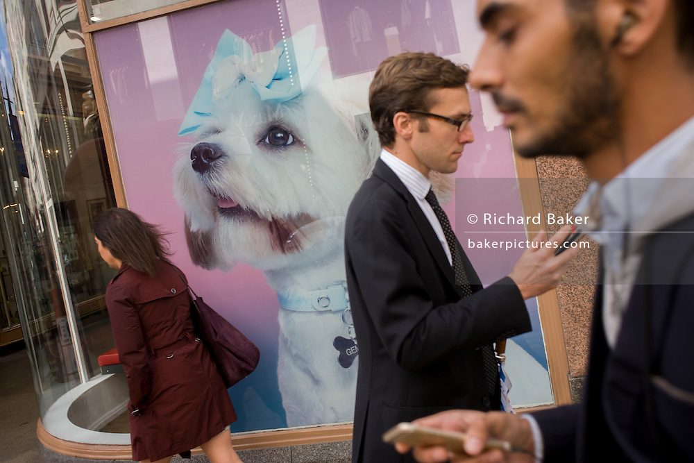 Passers-by and a fluffy pooch on a Camper shoes shop window in Bond Street, central London.