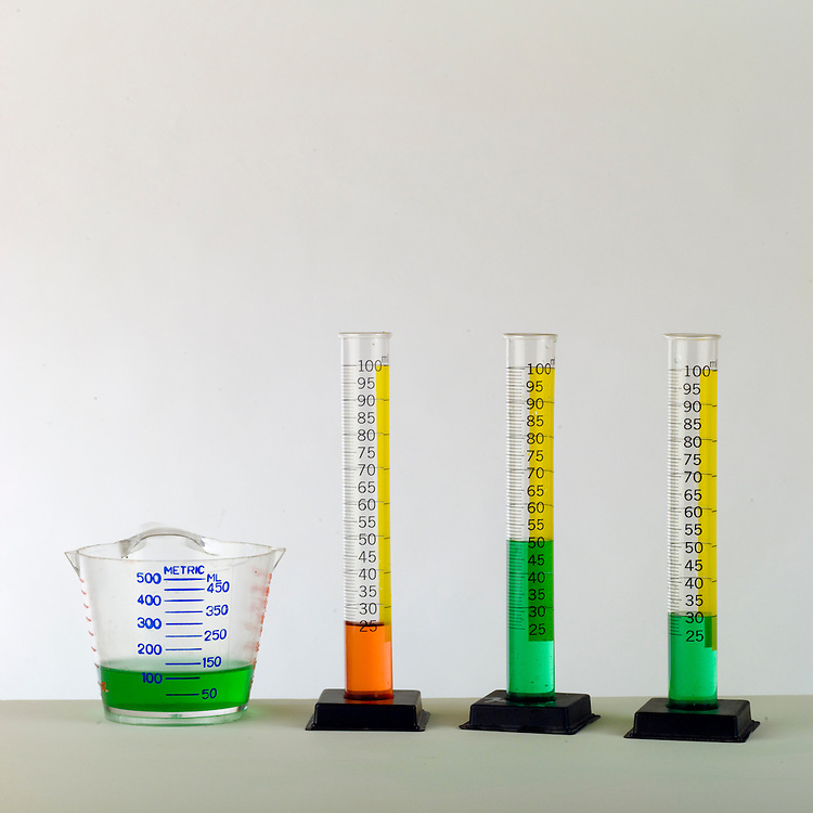 Volumes of liquid being measured  in a measuring cup and graduated cylinders.