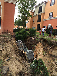 A family looks at a crack in the earth along the foundation of a building at the Landmark at West Place Apartments after Hurricane Irma hit Central Florida on Monday, September 11, 2017. Photo by Mary Shanklin/Orlando Sentinel/TNS/ABACAPRESS.COM