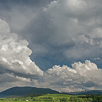 Summer thunderstorm clouds build over pastures in the Gallatin Valley and mountains of the Gallatin Range south of Bozeman, Montana.
