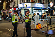 "Police are seen observing the area, meanwhile, people enjoying a late night out in Soho, in London's West End on Sunday, Sept 13, 2020. The public has been urged to act ""in tune"" with Covid-19 guidelines before the ""rule of six"" restrictions come into force on Monday. The British government's scientific advisory board announced on Friday that the reproduction number of coronavirus transmission across the UK was now over 1.0. The Science and the Scientific Advisory Group for Emergencies (SAGE) said the R-value was now between 1.0 and 1.2. (VXP Photo/ Vudi Xhymshiti)"