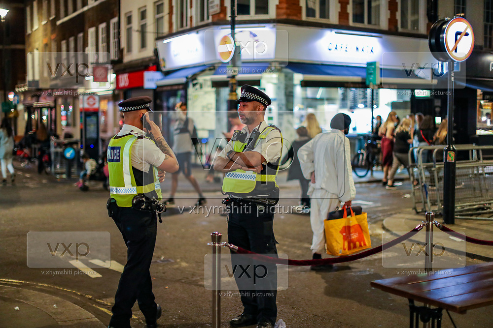 """Police are seen observing the area, meanwhile, people enjoying a late night out in Soho, in London's West End on Sunday, Sept 13, 2020. The public has been urged to act """"in tune"""" with Covid-19 guidelines before the """"rule of six"""" restrictions come into force on Monday. The British government's scientific advisory board announced on Friday that the reproduction number of coronavirus transmission across the UK was now over 1.0. The Science and the Scientific Advisory Group for Emergencies (SAGE) said the R-value was now between 1.0 and 1.2. (VXP Photo/ Vudi Xhymshiti)"""