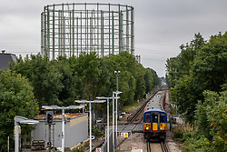 Licensed to London News Pictures. 07/10/2021. London, UK. Disused gas holders which were used in the 1930's to store domestic gas for local homes, tower over Motspur Park Station in south-west London as analysts predict that household energy bills could soar by £400 by next year as the wholesale price of gas hits new highs. Industry leaders have also warned that the high gas price, HGV lorry driver shortage and petrol stations running empty will have a kock-on effect and lead to higher prices for food in supermarkets. Photo credit: Alex Lentati/LNP