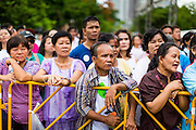 "15 JUNE 2014 - BANGKOK, THAILAND: Thai civilians wait to get into a ""Return Happiness to Thais"" party in Lumpini Park in Bangkok. The Thai military junta, formally called the National Council for Peace and Order (NCPO), is sponsoring a series of events throughout Thailand to restore ""Happiness to Thais."" The events feature live music, dancing girls, military and police choirs, health screenings and free food.   PHOTO BY JACK KURTZ"