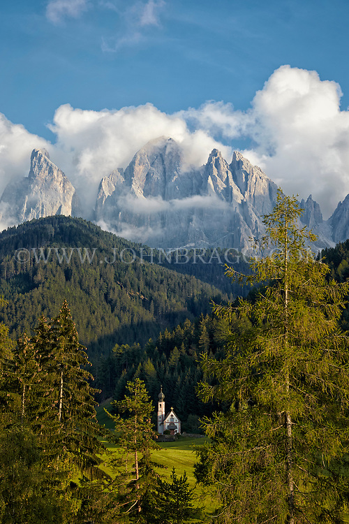 St. Johann Church in Val di Funes with the Dolomites mountain range in the distance.