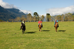Chile, Lake Country: People riding horses at Peulla in a meadow in the Andes..Photo #: ch601-33247..Photo copyright Lee Foster www.fostertravel.com, lee@fostertravel.com, 510-549-2202.