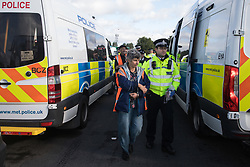 Colnbrook, UK. 27th September, 2021. Metropolitan Police officers arrest Insulate Britain climate activists who had previously blocked a slip road from the M25 at Junction 14 close to Heathrow airport as part of a campaign intended to push the UK government to make significant legislative change to start lowering emissions. The activists are demanding that the government immediately promises both to fully fund and ensure the insulation of all social housing in Britain by 2025 and to produce within four months a legally binding national plan to fully fund and ensure the full low-energy and low-carbon whole-house retrofit, with no externalised costs, of all homes in Britain by 2030.