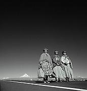 Three ladies in traditional dress with Nevado Sajama volcano in background, Tomarapi, Sajama National Park, Oruro, Bolivia