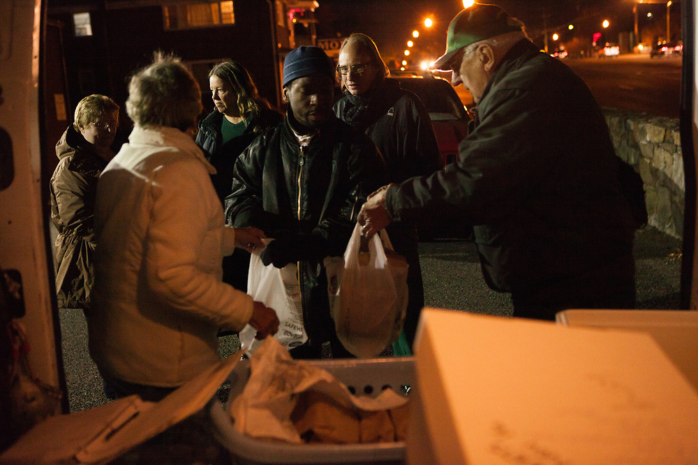"""FAIRFAX, VA – NOVEMBER, 2012: A group of homeless men and women receive a free meal from FACETS, a local nonprofit that seeks to end homelessness by transforming lives through Christian spirituality, counseling and service. """"They've helped me tremendously,"""" said Susan Allen, age 63. """"I don't know where I'd be without FACETS.<br /> <br /> As the economic downturn trickles through the American job market, a rising number of middle class workers are finding themselves on the verge of homelessness. Susan Allen, 63, worked most of her adult life as a legal administrative assistant – a career that afforded her a comfortable, but modest lifestyle. Allen didn't save much of her income, and without family members to rely on after losing her job in the 2008 recession, Allen was forced to dip into what savings she had to stay afloat. Two years later, following a succession of layoffs from part-time jobs, Allen eventually succumbed to homelessness.<br /> <br /> Today, Susan Allen lives out of her 2006 Saturn Ion – her most valuable asset – while struggling to meet her basic needs. The perpetual search for employment has proven difficult for her and job-seekers like her across the country, who near retirement age find themselves thrust back into the most competitive job market the United States has seen in decades. Yet despite her challenges, Allen remains hopeful. As someone who used to think she was firmly planted in the middle class, she believes fear drives most people's attitudes toward the homeless. """"You think you're never going to be in that situation,"""" Allen said. """"But now when you see people who are down and out, maybe you realize you're only one or two paychecks away from that yourself. That's why so many people turn away from me,"""" Allen says. """"I'm a constant reminder of what might happen to them."""""""