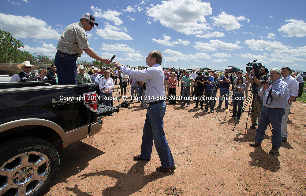 Texas Lt. Gov. David Dewhurst accepts the microphone from Texas landowner Tommy Henderson during a gathering of politicians, landowners, law enforcement and media at the bridge over the Red River on Highway 79, northeast of Byers, Texas on April 28, 2014. Dewhurst was present to voice support for Henderson in his fight with the BLM over land he says he paid for and owns.