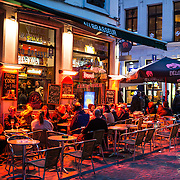 Patrons eat and drink at outdoor seating outside a pub / bar in the old town of Brussels, Belgium, at night.