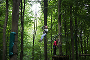 A small girl rides across a zip wire high up in the trees in Vejle,Denmark, 14th of August 2016. Gorilla Park is an adventure play ground set high up in the trees demanding balance and no fear of hights.