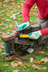 Cleaning the underneath of a lawnmower in autumn. Using a hand brush to clean the blades