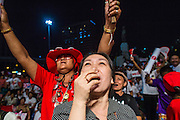 01 MARCH 2013 - BANGKOK, THAILAND: <br /> Thai women cheer for NATTAWUT SAI-KUA (not in picture) during the last election rally Pongsapat Pongchareon who is running for governor of Bangkok Nattuwat is a popular Red Shirt leader and member of Thai Parliament from the Pheu Thai party. The election is Sunday, March 3 and no campaigning is allowed 24 hours before election day. Police General Pongsapat Pongcharoen (retired), a former deputy national police chief who also served as secretary-general of the Narcotics Control Board is the Pheu Thai Party candidate in the upcoming Bangkok governor's election. He resigned from the police force to run for Governor. Former Prime Minister Thaksin Shinawatra reportedly personally recruited Pongsapat. Most of Thailand's reputable polls have reported that Pongsapat is leading in the race and likely to defeat Sukhumbhand Paribatra, the Thai Democrats' candidate and incumbent. The loss of Bangkok would be a serious blow to the Democrats, whose national base has been the Bangkok area.    PHOTO BY JACK KURTZ