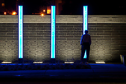 A man stops to view the I-35W Bridge Memorial along the river bank of the Mississippi River in downtown Minneapolis, MN