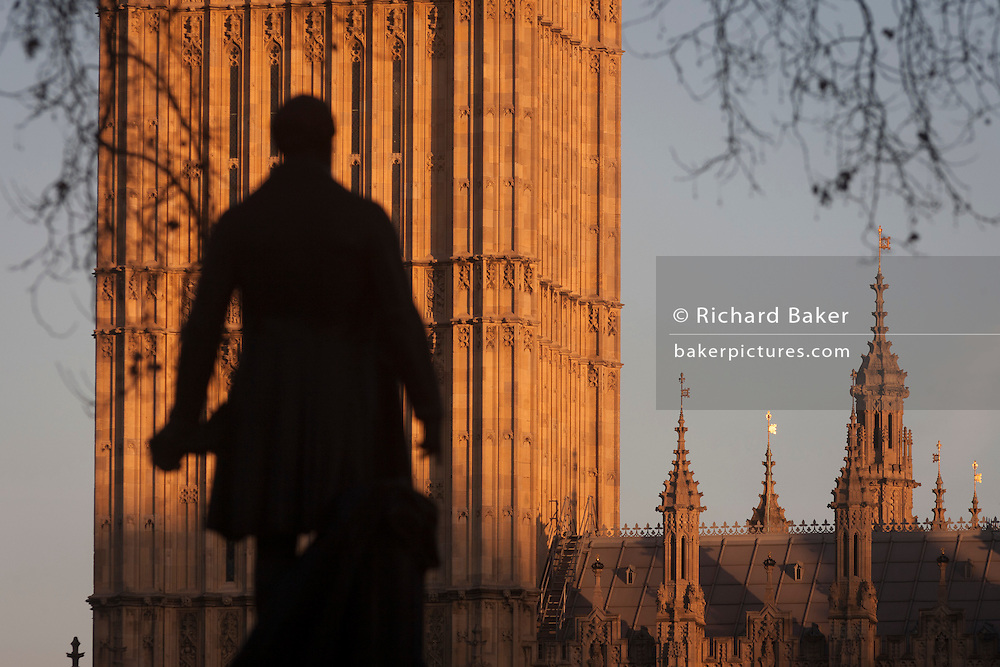 """The silhouetted statue of Sir Robert Peel and the Elizabeth Tower of the British parliament, on 17th January 2017, in London England. The Elizabeth Tower (previously called the Clock Tower) named in tribute to Queen Elizabeth II in her Diamond Jubilee year – was raised as a part of Charles Barry's design for a new palace, after the old Palace of Westminster was largely destroyed by fire on the night of 16 October 1834. The new Parliament was built in a Neo-gothic style, completed in 1858 and is one of the most prominent symbols of both London and England. Sir Robert Peel, was a British statesman and member of the Conservative Party, served twice as Prime Minister of the United Kingdom and twice as Home Secretary. He created the modern police force and officers known as """"bobbies"""" and """"peelers"""""""