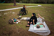 Riad Alsaloum rests on a mattress while wife Jamila Alrazouk keeps an eye on grandchildren Riad, 1, and Ahmad, 4, at Rowlett Park in Tampa, Florida, U.S. The Alsaloum family made the trip for a refugee picnic hosted by Coptic Orthodox Charities, their resettlement agency. As Riad Alsaloum's health deteriorated, it became increasingly difficult for his family to prevent discomfort for him.