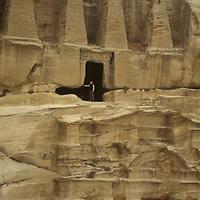 A traveler investigates the Obelisk tombs in the ancient Nabatean ruins at Petra, Jordan.