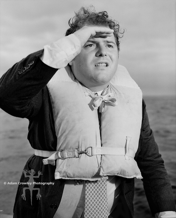 Businessman wearing a life vest, and shielding his eyes (B&W)