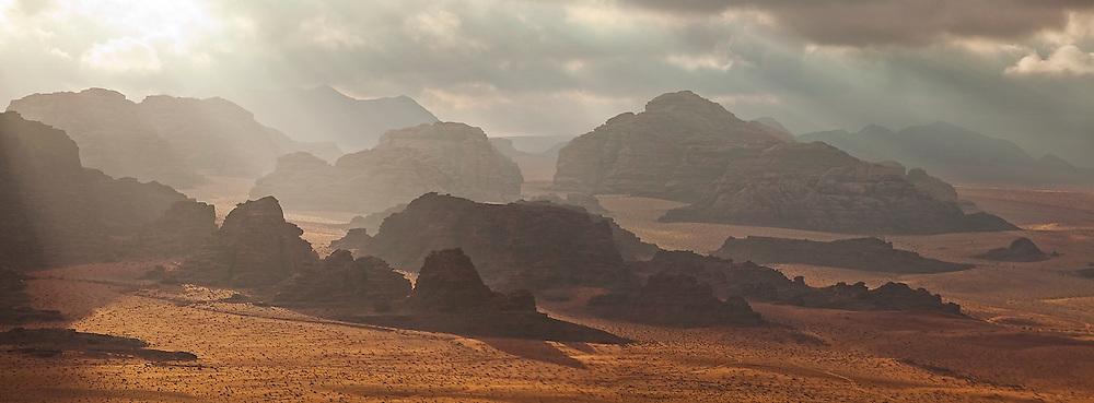 Shafts of light filter through dark clouds onto sandstone cliffs in Wadi Rum, Jordan.