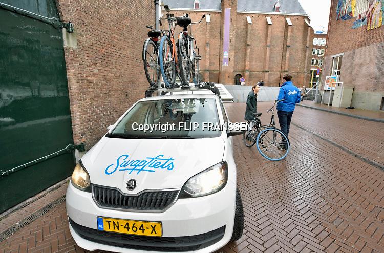 Nederland, Nijmegen, 22-12-2018 Een medewerker van Swapfiets.nl helpt een klant die een probleem heeft met haar gehuurde fiets . Swapfiets verhuurt fietsen met de garatie van reparatie onderhoud en vervangend vervoer . Foto: Flip Franssen