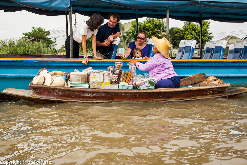 """17 NOVEMBER 2012 - BANGKOK, THAILAND:  A woman selling tourist curios alongside a tourist boat on the Chao Phraya River in Bangkok. Bangkok used to be known as the """"Venice of the East"""" because of the number of waterways the criss crossed the city. Now most of the waterways have been filled in but boats and ships still play an important role in daily life in Bangkok. Thousands of people commute to work daily on the Chao Phraya Express Boats and fast boats that ply Khlong Saen Saeb or use boats to get around on the canals on the Thonburi side of the river. Boats are used to haul commodities through the city to deep water ports for export.    PHOTO BY JACK KURTZ"""