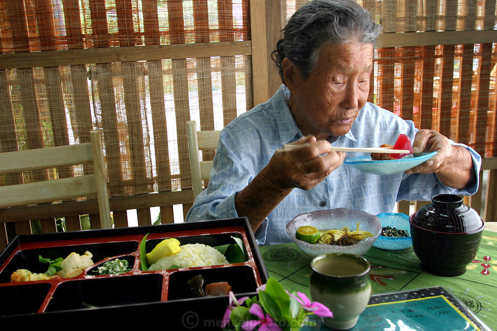 "At a ""longevity restaurant"" (an eatery claiming to serve food that will make patrons live longer) in Ogimi, Okinawa, 96-year-old Matsu Taira finishes the long-life lunch with a jellied fruit dessert made from bright-red acerola berries. Hungry Planet: What the World Eats (p. 192). Hara hachi bu: ""eat only until 80 percent full,"" say older Okinawans. The island has been the focus in recent years of researchers trying to discover why a disproportionately large number of Okinawans are living to age 100 or more. This image is featured alongside the Matsuda family images in Hungry Planet: What the World Eats."
