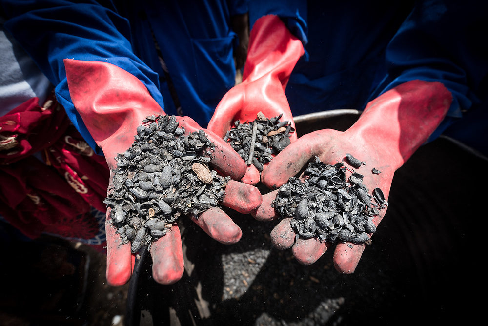30 May 2019, Mokolo, Cameroon: Burnt biomass awaits further processing, soon to become charcoal. At the Minawao camp for Nigerian refugees, degradable and non-degradable waste are separated, so that biomass can be burnt in metal containers, processed and finally transformed into charcoal briquettes as a source of recycled energy to be used as firewood for cooking. With the support of an environment monitor  from the Lutheran World Federation World Service programme, the full process from waste to charcoal is managed and run by the refugees themselves. The Minawao camp for Nigerian refugees, located in the Far North region of Cameroon, hosts some 58,000 refugees from North East Nigeria. The refugees are supported by the Lutheran World Federation, together with a range of partners.