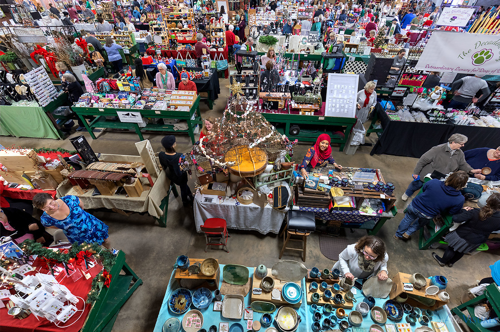 The Greensboro Farmers Curb Market Hosts MADE 4 the Holidays Arts, Crafts, & Pottery Shows was held twice in 2018.<br /> <br /> The Market is an indoor facility with free admission, Wi-Fi, and plenty of free parking as well as an ATM on site.<br /> <br /> Photographed, Sunday, December 2, 2018, in Greensboro, N.C. JERRY WOLFORD and SCOTT MUTHERSBAUGH / Perfecta Visuals<br /> <br /> Greensboro, NC – The public is invited to the MADE 4 the Holidays Arts, Crafts, & Pottery shows which are scheduled for Sunday, November 11th, 2018 and Sunday, December 2nd, 2018 at the Greensboro Farmers Curb Market (501 Yanceyville Street) with free entrance from 11 am – 4 pm.<br /> The MADE 4 the Holiday shows are the area's largest local juried holiday show. All products are local made arts, crafts, & pottery that showcase over 100 emerging and favorite returning unique artisans from around the Piedmont and surrounding areas.  The artists bring a variety of handcrafted jewelry, pottery, wood, fiber art, fine art, body care, packaged, NC-made artisan foods, and so much more!<br /> <br /> General admission is free starting at 11 am. Early access can be purchased with the Early Bird Tickets for just $5. Early Bird customers have the opportunity to begin shopping the shows starting at 10 am and get entered into up to two raffles per show. Patrons can purchase tickets online at least a week before the event and get entered into an exclusive online raffle before the show or purchase tickets up to 11 am the day-of for a chance at the door-prize raffle. Raffle prizes are different for each show and are made up of handmade crafts and products from vendors of the show.<br /> Early Bird Tickets for both the November 11th show and December 2nd show can be purchased online at Eventbrite.<br /> While shopping customers can enjoy live music by various artists for each of the shows:<br /> November 11th: Adam Doyle will be performing live keyboard easy listening from 11:30 am to 1 pm and John Stevens 