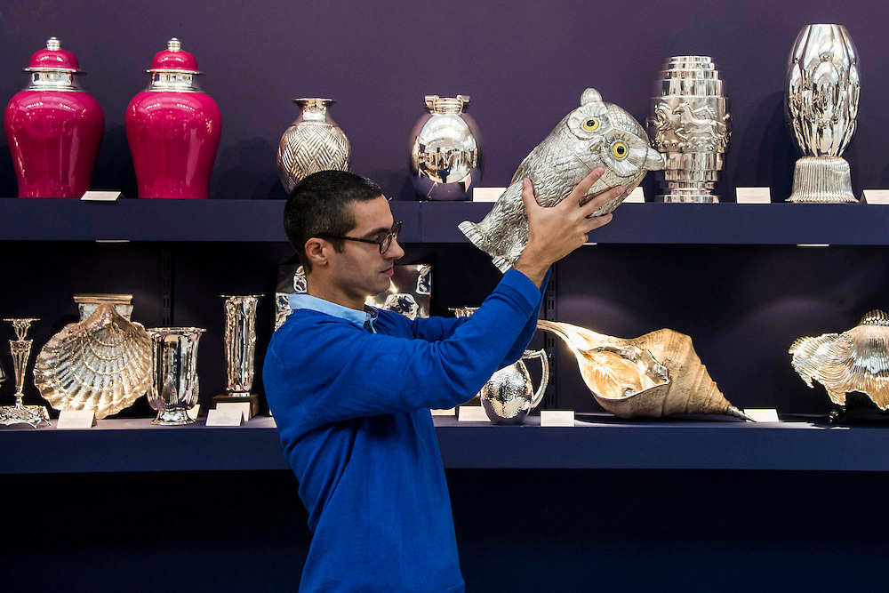 A silver owl wine cooler (£10k) is inspected on the J Baptista Antiquario stand - Winter Olympia Art & Antiques Fair- in its 25th year the fair plays host to 22,000 visitors who come to see over 30,000 pieces for sale from the 120 hand-picked dealers valued frpom £100-£1m.  The fair runs from 2-8 November 2015, opening with the Collector's Preview Reception on 2 November at 5pm..