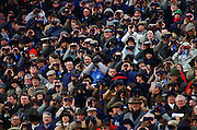 Racegoers watch racing at Cheltenham Races, Gloucestershire, United Kingdom